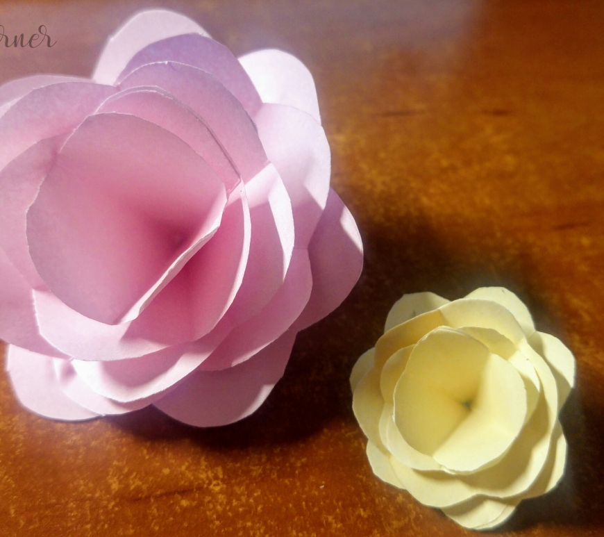 Two completed paper roses: pink and yellow