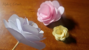 Three completed paper roses: white, yellow and pink