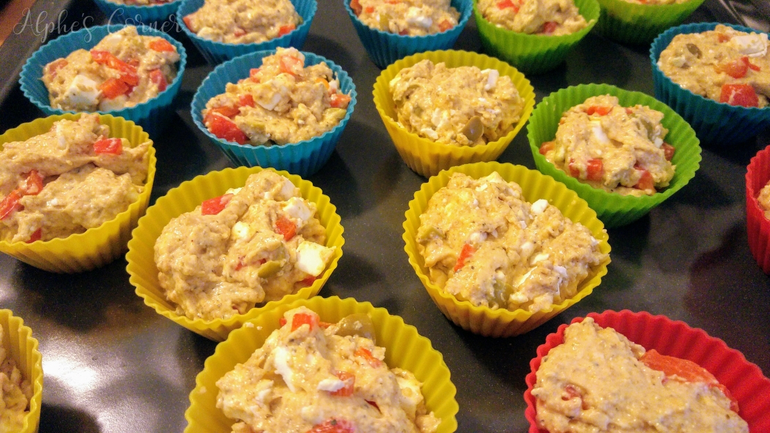 Raw feta, olives and bell pepper muffins in the moulds