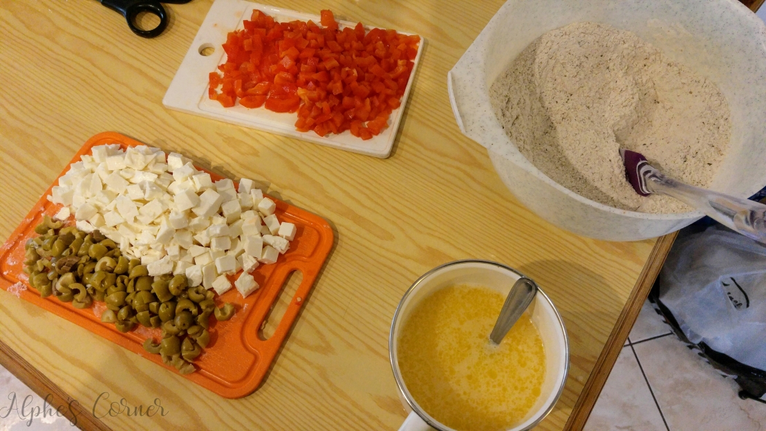 Chopped up feta cheese, olives and peppers and flour in a bowl
