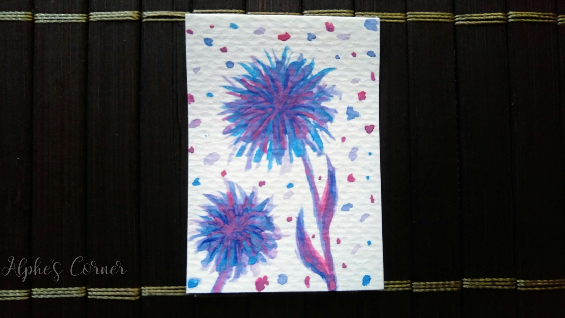 A small paper tag with pink and purple watercolour dandelions