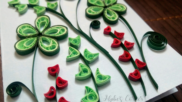 A quilled card with green and red flowers