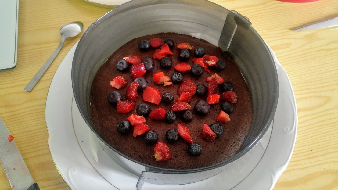 Chocolate base cake with fruits on top, in a cake ring
