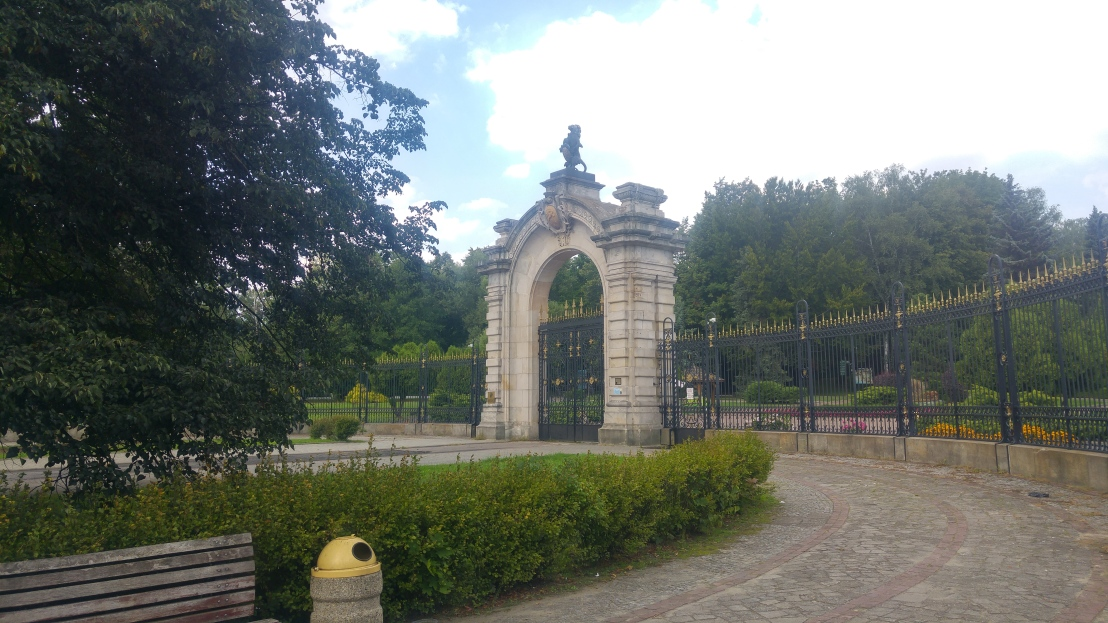 A decorative, huge marble gate and a black and gold fence