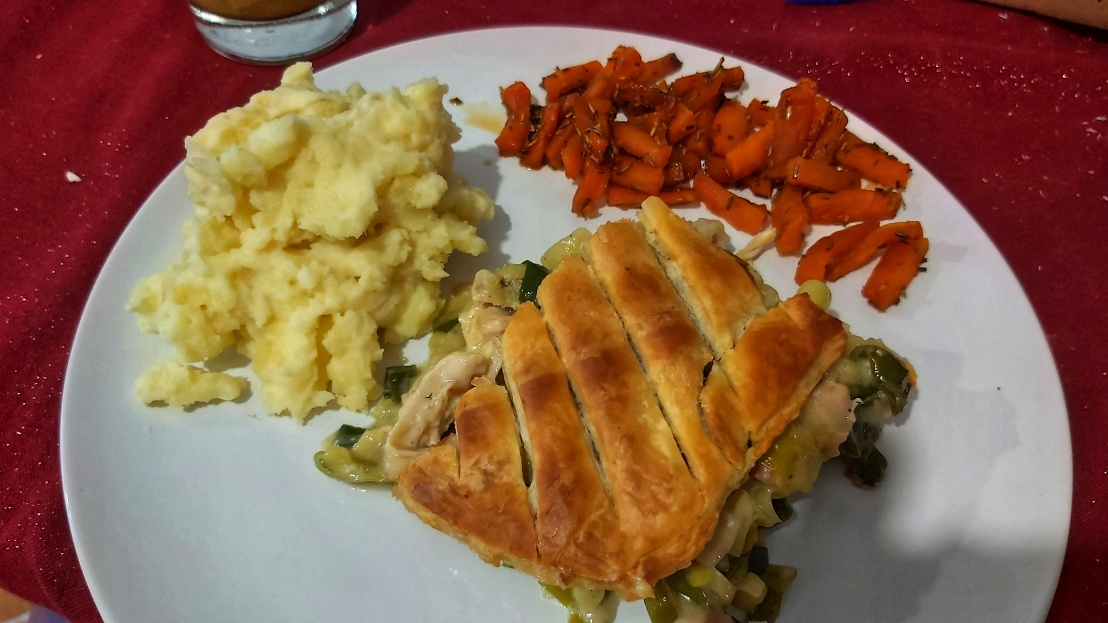 Chicken and leek pie on a plate with mashed potatoes and glazed carrots