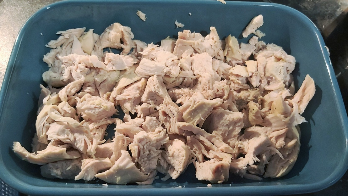 Shredded cooked chicken breast in an ovenproof dish