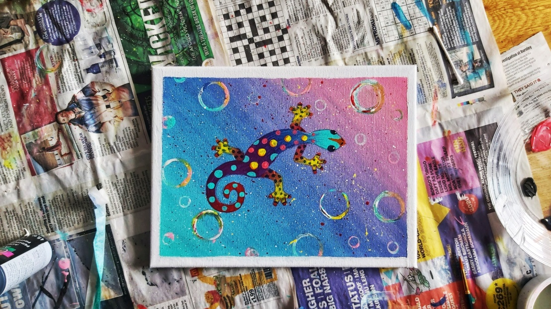 A painted colourful acrylic gecko on a canvas