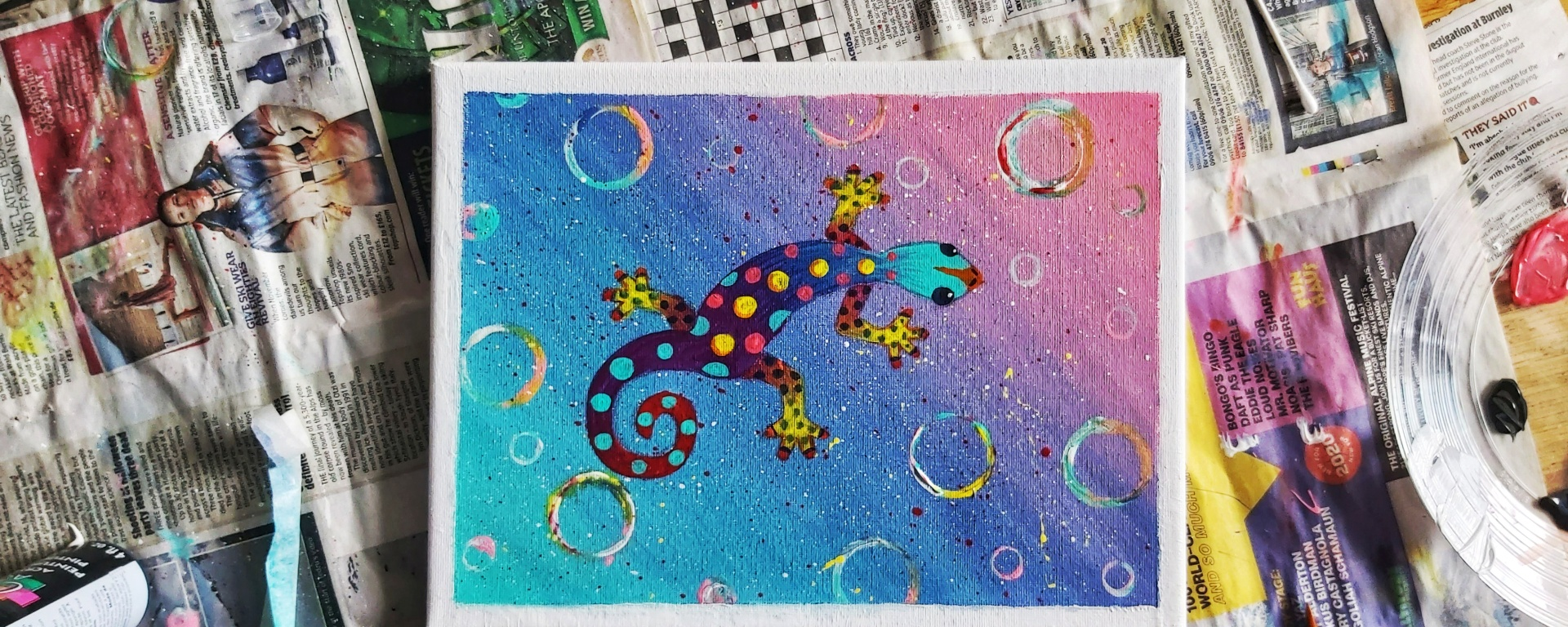 A painted colourful acrylic gecko on a canvas