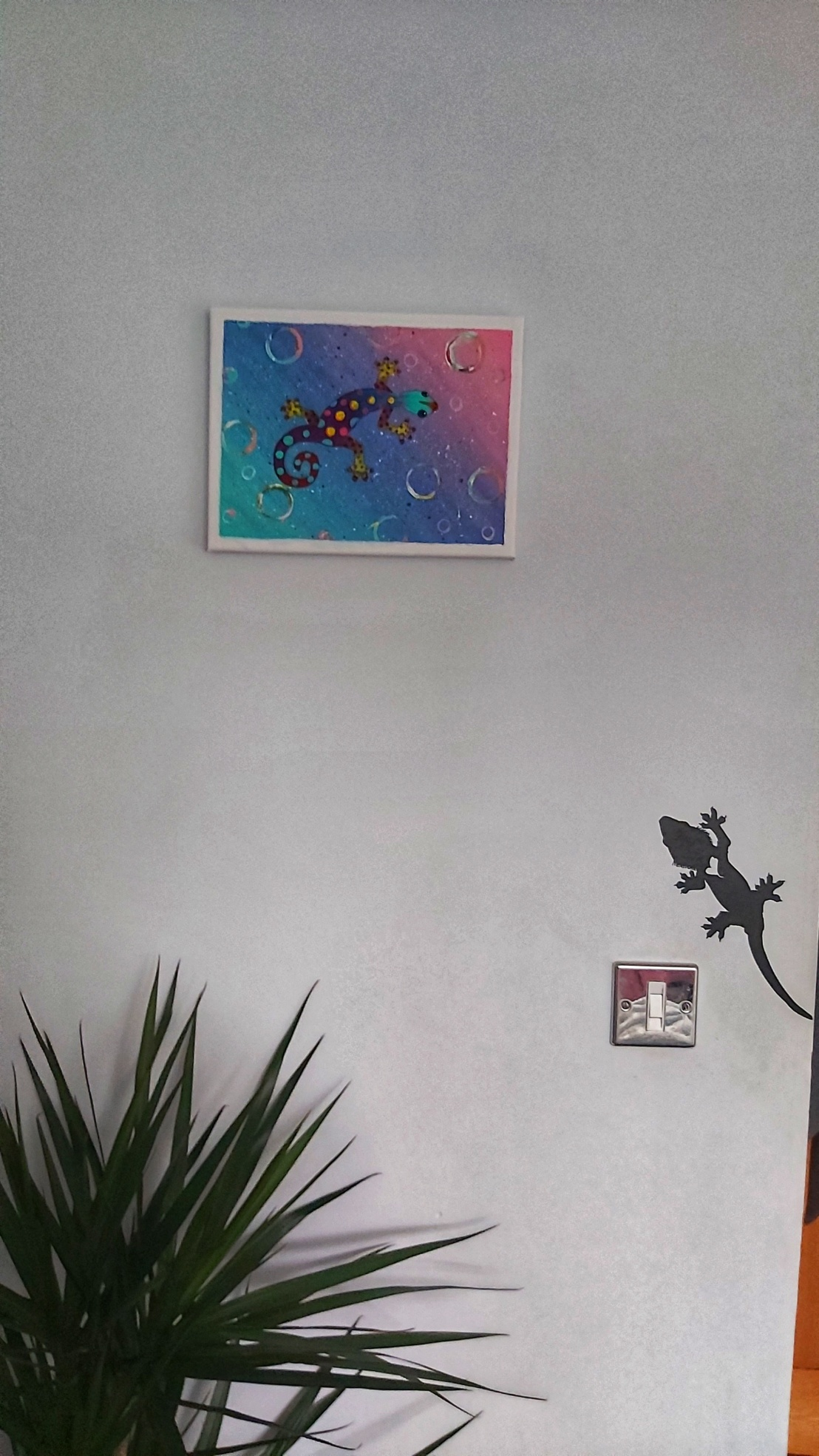 Acrylic gecko painting hanging on a wall