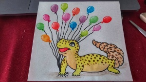 A finished card of a watercolour gecko holding balloons