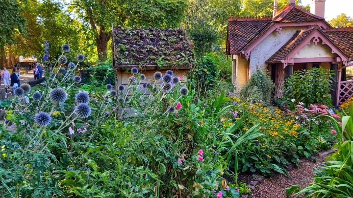 A small gardener's house surrounded by flowers