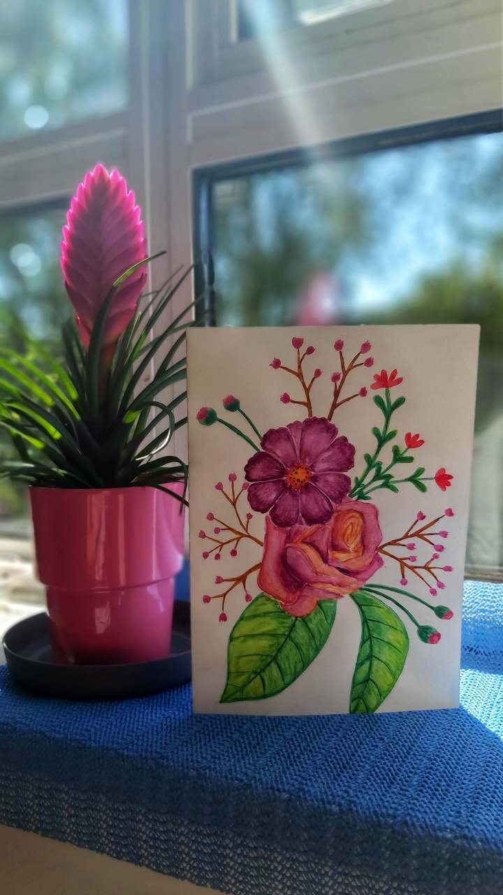 A floral watercolour card next to a flower