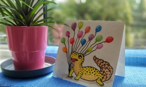 A watercolour gecko card on a windowsill next to a flower