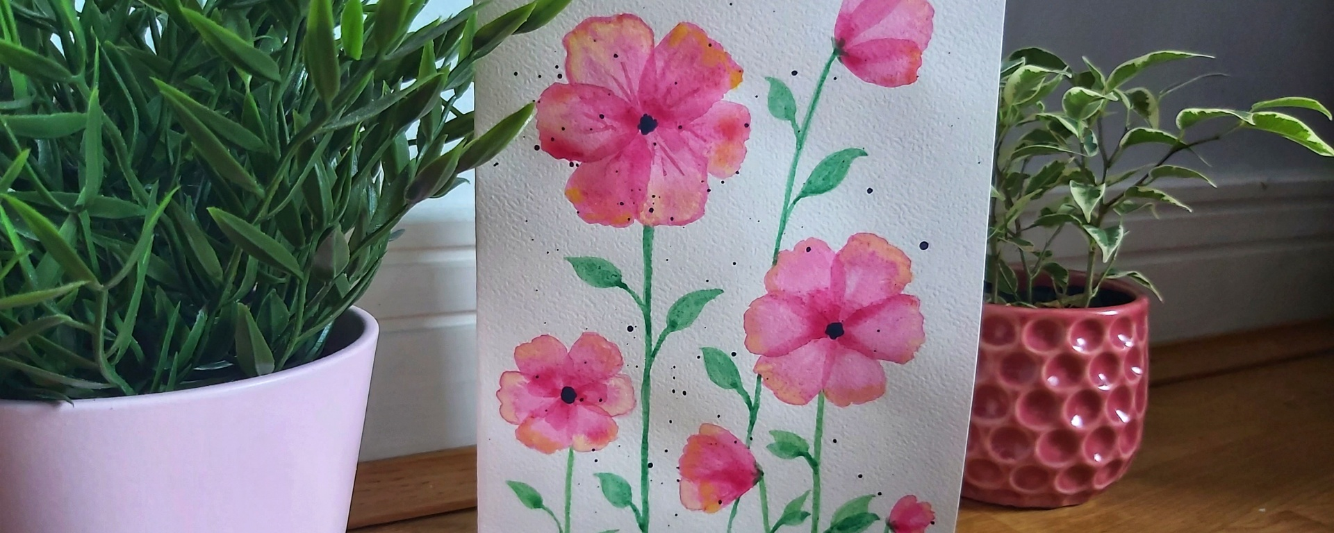 Completed pink watercolour poppies card between two flower pots