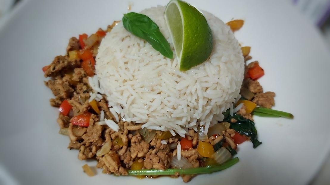 Zesty Thai Basil Pork on a plate, with rice, basil and lime