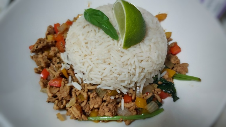 Zesty Thai Basil Pork on a plate, with rice, basil and lime