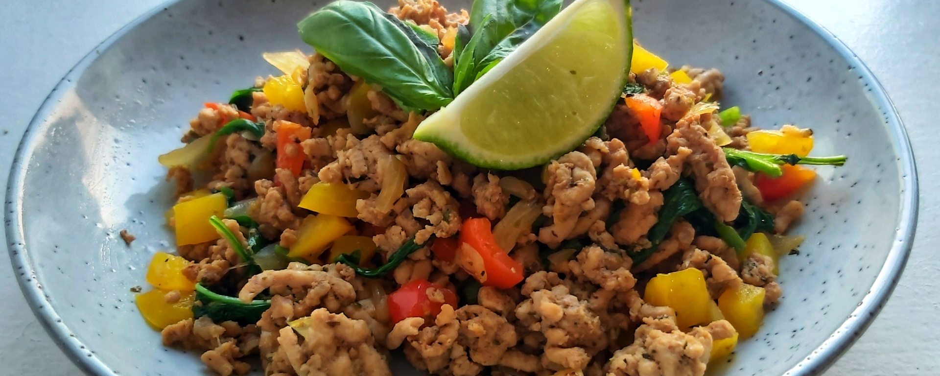 Zesty Thai Basil Pork on a plate, garnished with basil and lime