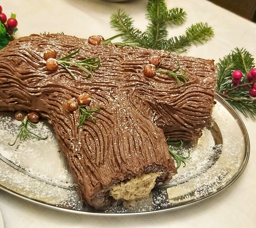 Hazelnut Yule Log Cake on a decorated table with holly